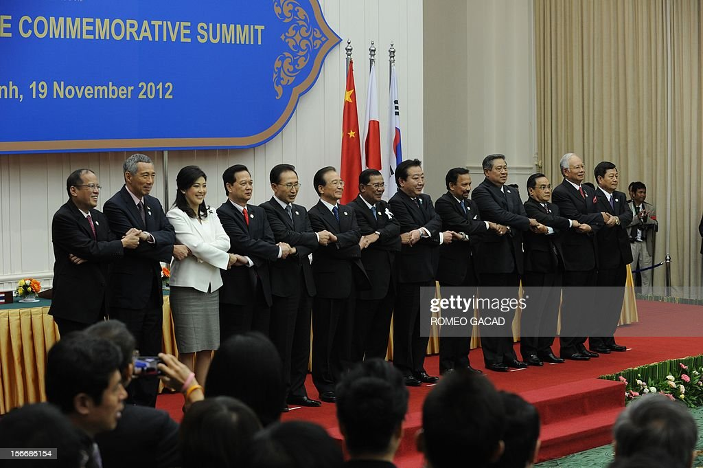 Philippines President Benigno Aquino, Singapore Prime Minister Lee Hsien Loong, Thai Prime Minister Yingluck Shinawatra, Vietnamese Prime Minister Nguyen Tan Dung, South Korean President Lee Myung Bak, Chinese Premier Wen Jiabao, Cambodian Prime Minister Hun Sen, Japan Prime Minister Yoshihiko Noda, Brunei Sultan Hassanal Bolkiah, Indonesian President Susilo Bambang Yudhoyono, Laos Prime Minister Thongsing Thammavong, Malaysian Prime Minister Najib Razak and Myanmar Deputy Foreign Minister Kan Zaw join hands together for a family photo session during the Association of Southeast Asian Nations (ASEAN) Plus Three Commemorative Summit in Phnom Penh on November 19, 2012 following the 21st ASEAN Leaders Summit.