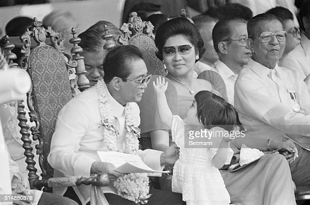 Philippines President Ferdinand Marcos and his wife Imelda play with their threeyearold niece Aimee while presiding over Independence Day celebrations
