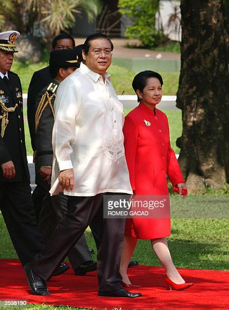 Philippines President Gloria Arroyo walks with her husband Jose Miguel Arroyo at the Malacanang presidential palace 14 July 2003 Opposition Senator...