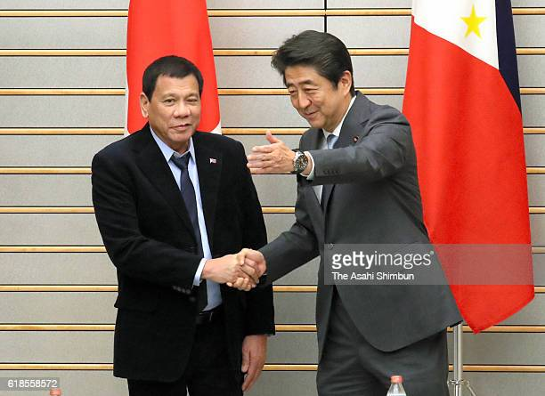 Philippines President Rodrigo Duterte and Japanese Prime Minister Shinzo Abe shake hands prior to their meeting at Abe's official residence on...