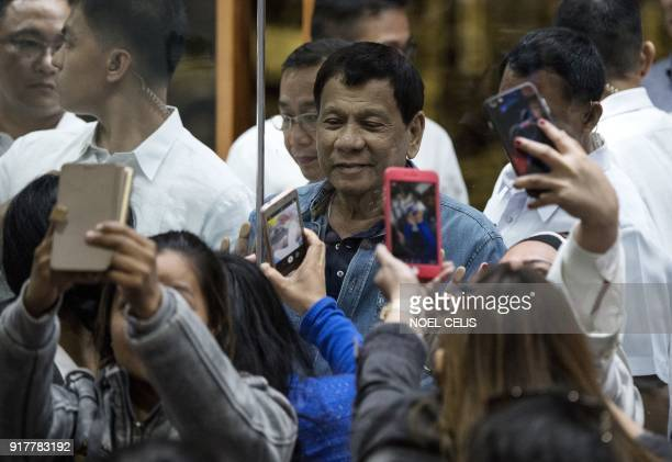 Philippine's President Rodrigo Duterte pose for a selfie through a glass wall for overseas Filipino workers that arrived in Manila from Kuwait at...