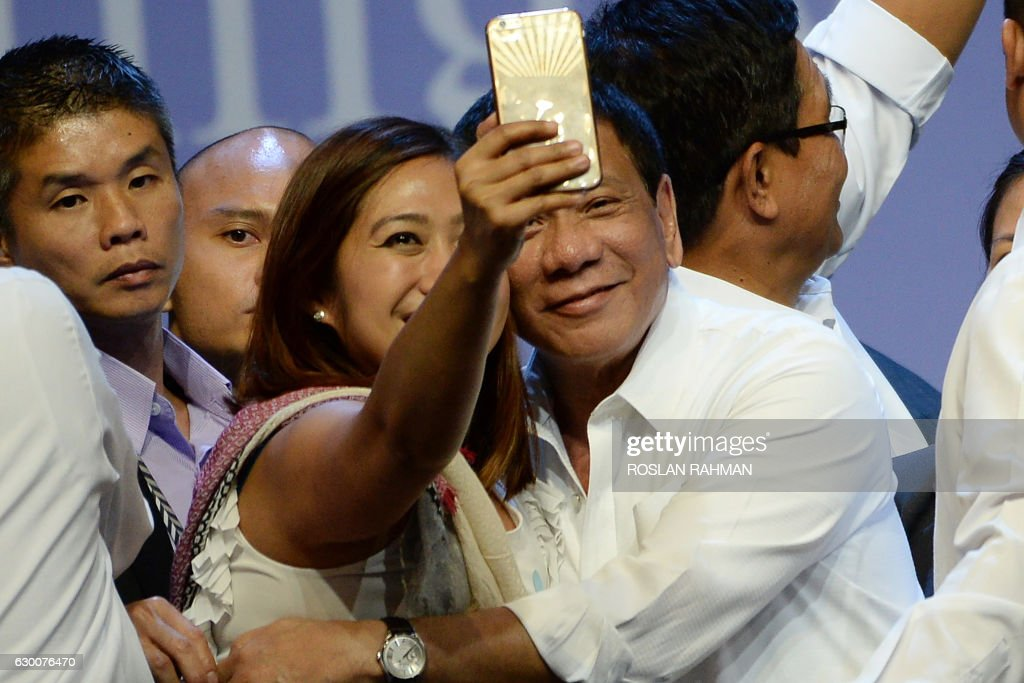 Philippines President Rodrigo Duterte (R) poses for a selfie during a meeting with the Filipino community in Singapore on December 16, 2016. Duterte is on a two-day state visit. / AFP PHOTO / ROSLAN RAHMAN / The erroneous mention[s] appearing in the metadata of this photo by ROSLAN RAHMAN has been modified in AFP systems in the following manner: [AFP] instead of [POOL]. Please immediately remove the erroneous mention[s] from all your online services and delete it (them) from your servers. If you have been authorized by AFP to distribute it (them) to third parties, please ensure that the same actions are carried out by them. Failure to promptly comply with these instructions will entail liability on your part for any continued or post notification usage. Therefore we thank you very much for all your attention and prompt action. We are sorry for the inconvenience this notification may cause and remain at your disposal for any further information you may require.