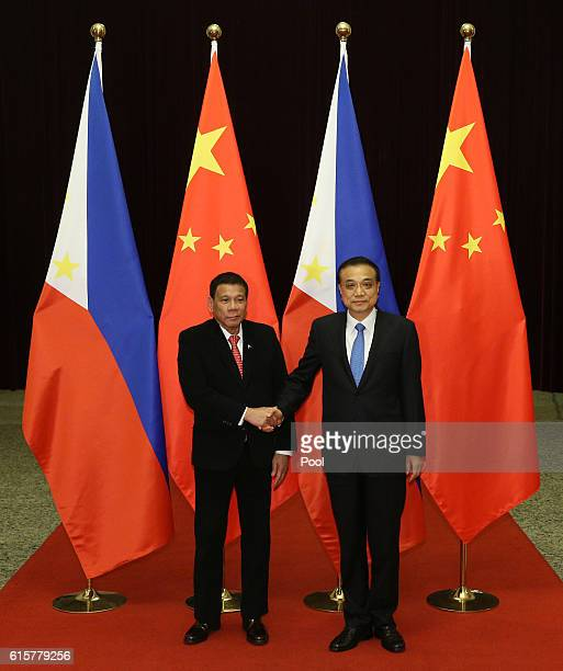 Philippines President Rodrigo Duterte shakes hands with Chinese Premier Li Keqiang ahead of their meeting at the Great Hall of the People on October...
