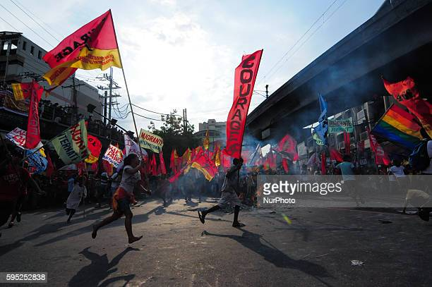 MANILA Philippines Protesters carrying their flags run around the effigy of Philippine President Benigno Aquino III engulfed in flames as thousands...