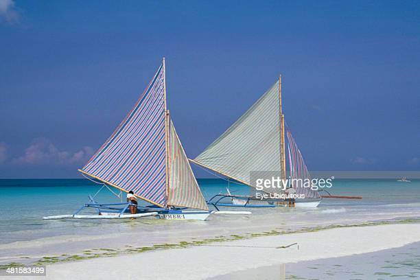 Philippines Visayan Islands Boracay Island Two outriggers with striped sails moored on the edge of a sandy beach