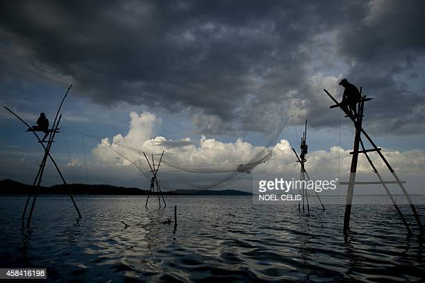 Philippines-typhoon,ADVANCER by Karl Malakunas This photo taken on October 14, 2014 shows fishermen raising an empty net at Barangay Anibong in...