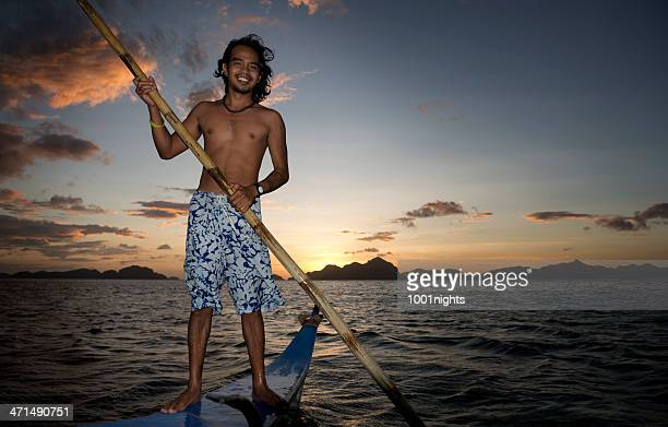 philippino on his traditional banca outrigger boats in the philippines - philippines stock pictures, royalty-free photos & images