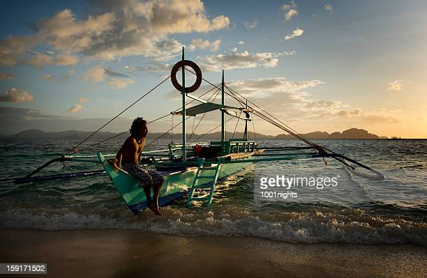 philippino with his traditional banca outrigger boats in the philippines
