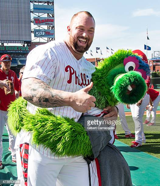 Phillie Phanatic tries to lift up Game of Thrones actor Hafthor Julius Bjornsson while participating in batting practice prior to The...