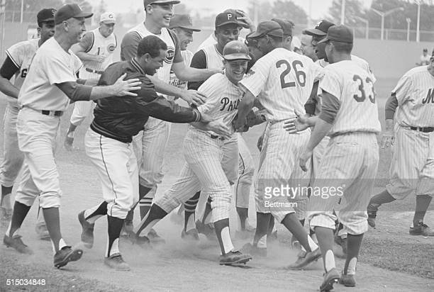Phillies outfielder Johnny Callison is mobbed by his National League teammates after he hit a ninth inning home run to break the 44 tie in the...