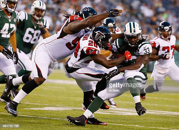 Phillip Adams of the Atlanta Falcons tackles running back Chris Ivory of the New York Jets during their pre season game at MetLife Stadium on August...
