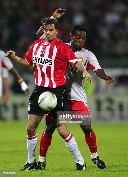 Phillip Cocu of PSV holds off Mickael Essien of Lyon during the UEFA Champions League Quarter - Final, first leg match between Olympique Lyonnais and...