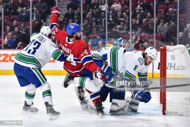 Phillip Danault of the Montreal Canadiens and Christopher Tanev of the Vancouver Canucks lose their balance during the second period at the Bell...