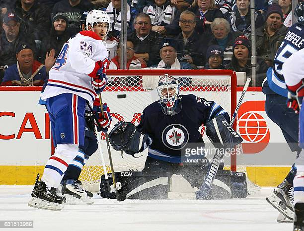 Phillip Danault of the Montreal Canadiens and goaltender Michael Hutchinson of the Winnipeg Jets keep an eye on the flying puck during second period...