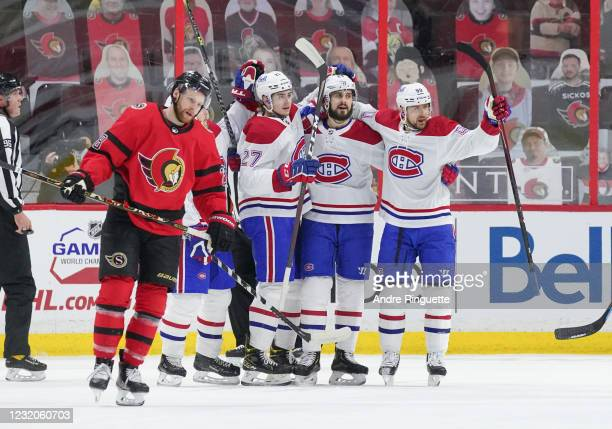 Phillip Danault of the Montreal Canadiens celebrates his first period goal with teammates Alexander Romanov and Tomas Tatar as Connor Brown of the...