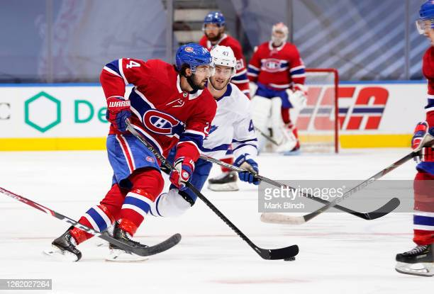 Phillip Danault of the Montreal Canadiens plays the puck as Pierre Engvall of the Toronto Maple Leafs pursues the play in the first period in an...
