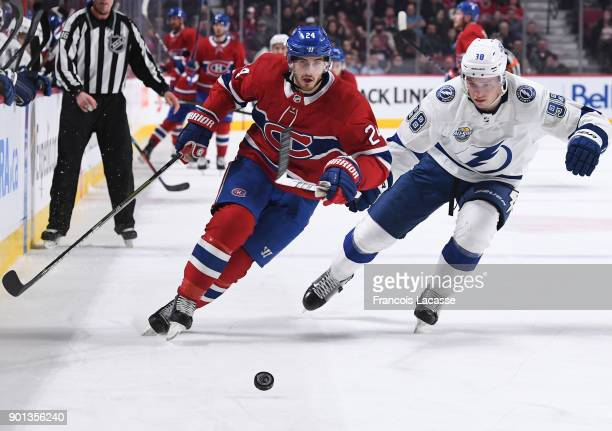 Phillip Danault of the Montreal Canadiens skates for the puck against Mikhail Sergachev of the Tampa Bay Lightning in the NHL game at the Bell Centre...