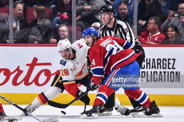 Phillip Danault of the Montreal Canadiens wins the faceoff against Elias Lindholm of the Calgary Flames during the first period at the Bell Centre on...