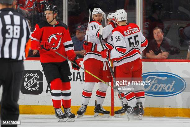 Phillip Di Giuseppe of the Carolina Hurricanes celebrates his first period goal with teammates as John Moore of the New Jersey Devils looks away...