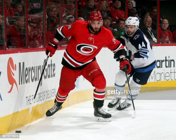 Phillip Di Giuseppe of the Carolina Hurricanes chases a puck along the end boards trailed by Josh Morrissey of the Winnipeg Jets during an NHL game...