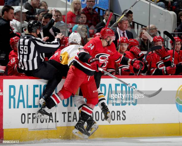 Phillip Di Giuseppe of the Carolina Hurricanes checks Olli Maata of the Pittsburgh Penguins into the boards as linesman Steve Barton is inadvertently...