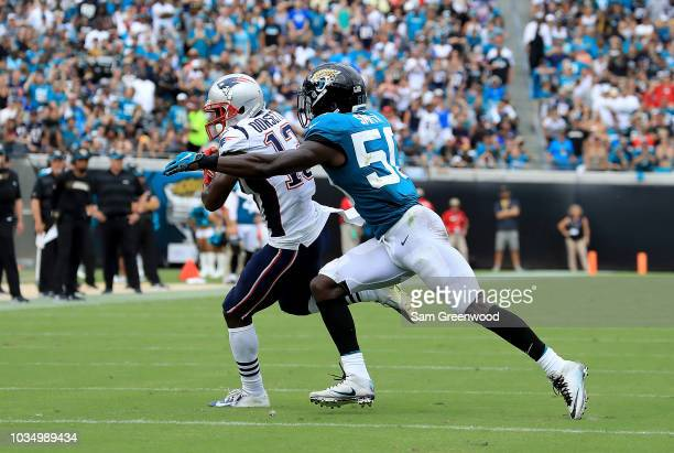 Phillip Dorsett of the New England Patriots is tackled by Telvin Smith of the Jacksonville Jaguars during the game at TIAA Bank Field on September 16...
