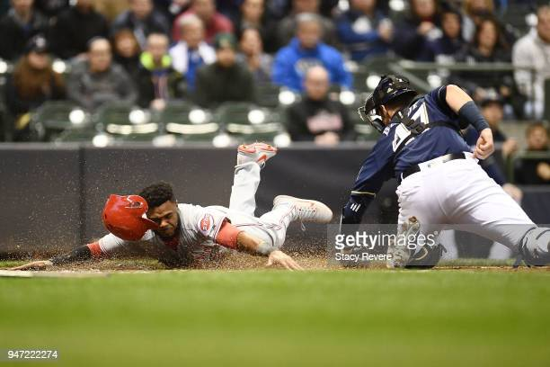 Phillip Ervin of the Cincinnati Reds beats a tag at home plate by Jett Bandy of the Milwaukee Brewers to score a run during the second inning at...