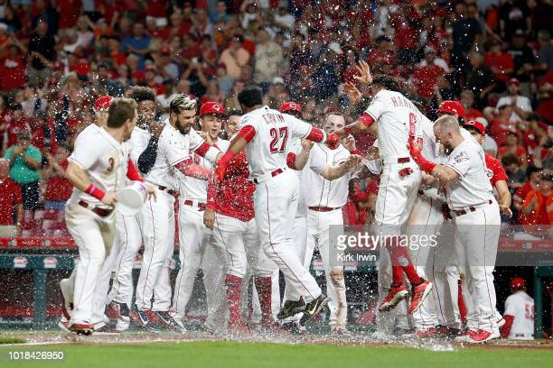 Phillip Ervin of the Cincinnati Reds is congratulated by his teammates at home plate after hitting a walk off home run off of Ray Black of the San...