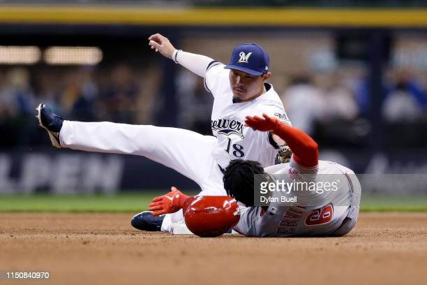 Phillip Ervin of the Cincinnati Reds slides into second base for a double past Keston Hiura of the Milwaukee Brewers in the first inning at Miller...