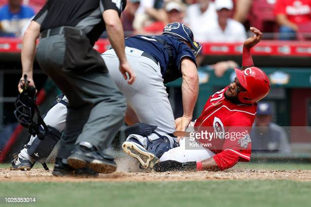 Phillip Ervin of the Cincinnati Reds slides under the tag of Erik Kratz of the Milwaukee Brewers to score a run during the seventh inning of the game...