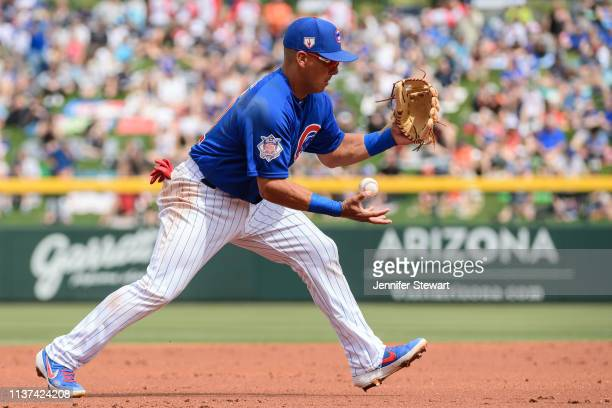 Phillip Evans of the Chicago Cubs bobbles the ball then makes the out at first during the spring training game against the San Francisco Giants at...