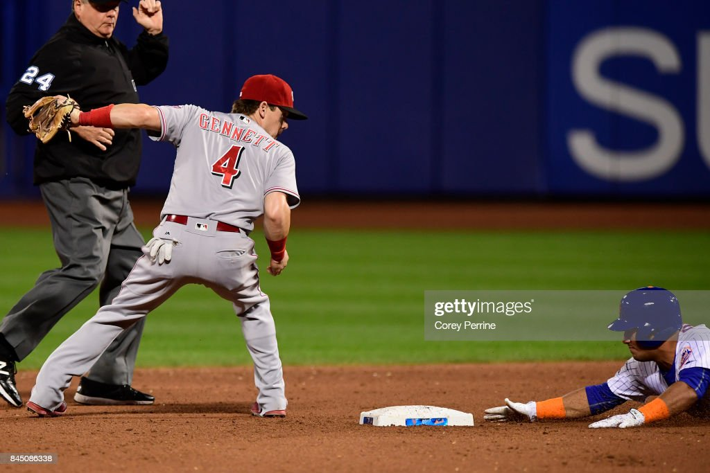 Phillip Evans #72 (R) of the New York Mets makes it safely to second base on a double as Scooter Gennett #4 of the Cincinnati Reds can't make the tag in time as umpire Jerry Layne #24 officiates during the fifth inning at Citi Field on September 9, 2017 in the Flushing neighborhood of the Queens borough of New York City. The Mets won 6-1.