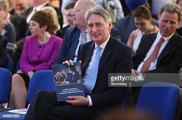 Phillip Hammond UK foreign secretary smiles as he holds a copy of the Conservative Party's 2015 general election manifesto at its launch in Swindon...