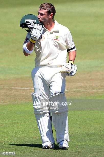 Phillip Hughes kisses the badge on his helmet after celebrating his 100 runs during day one of the Second Test between South Africa and Australia...