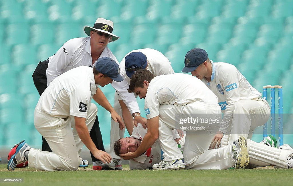 Phillip Hughes of South Australia is helped by New South Wales players after falling to the ground after being struck in the head by a delivery during day one of the Sheffield Shield match between New South Wales and South Australia at Sydney Cricket Ground on November 25, 2014 in Sydney, Australia.