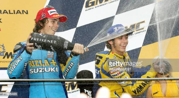Australian MotoGP rider Chris Vermeulen and Italian Valentino Rossi spray champagne after finishing second and third respectively in the Australian...