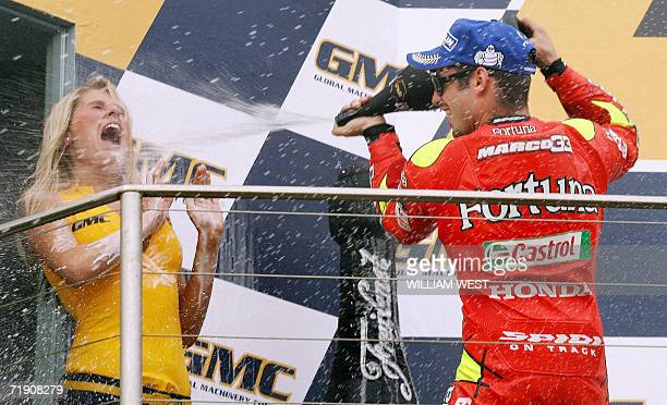 Italian MotoGP rider Marco Melandri sprays a promotional girl with champagne after winning the Australian Motorcycle Grand Prix at Phillip Island 17...