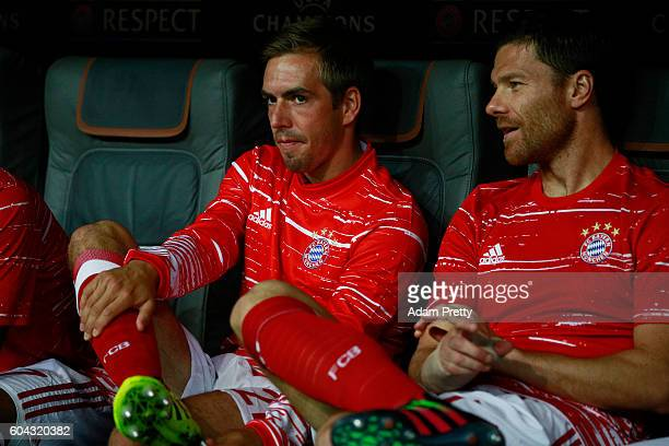 Phillip Lahm and Xabi Alonso of Bayern Muenchen look on from the bench during the UEFA Champions League Group D match between FC Bayern Muenchen and...