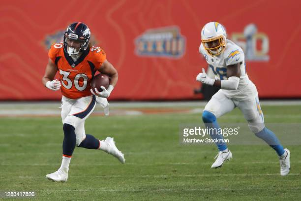 Phillip Lindsay of the Denver Broncos carries the ball against Casey Hayward Jr. #26 of the Los Angeles Chargers in the fourth quarter of the game at...