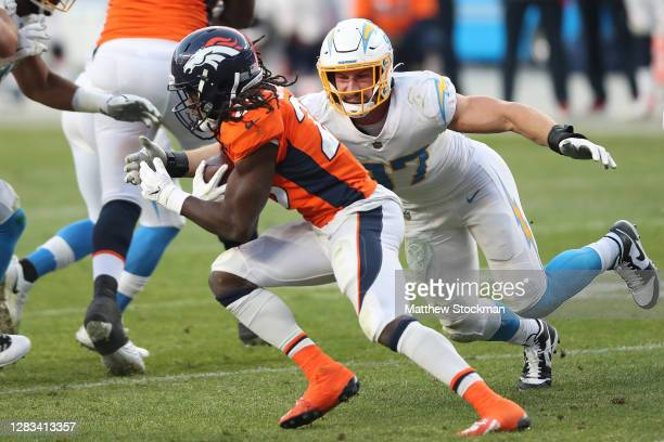 Phillip Lindsay of the Denver Broncos carries the ball against Joey Bosa of the Los Angeles Chargers in the third quarter of the game at Empower...