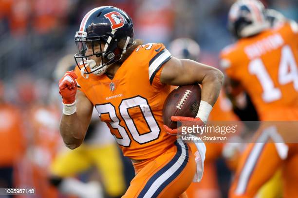 Phillip Lindsay of the Denver Broncos carries the ball against the Pittsburgh Steelers at Broncos Stadium at Mile High on November 25 2018 in Denver...