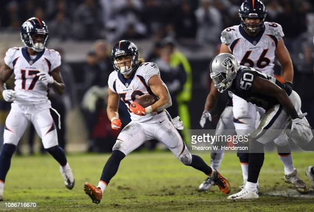 Phillip Lindsay of the Denver Broncos carries the ball against the Oakland Raiders during the first half of an NFL football game at OaklandAlameda...