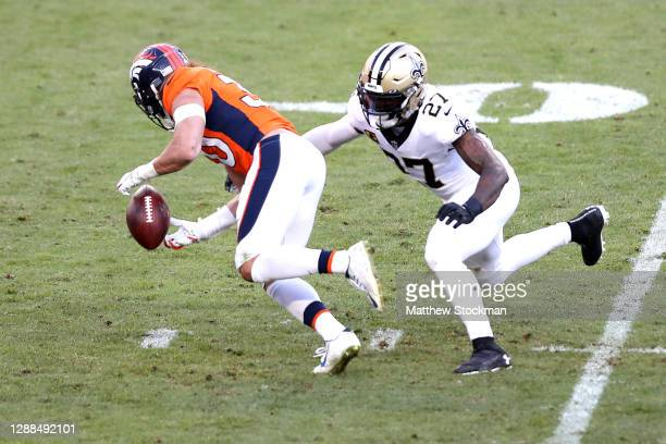 Phillip Lindsay of the Denver Broncos fumbles ahead of Malcolm Jenkins of the New Orleans Saints during the second quarter of a game at Empower Field...