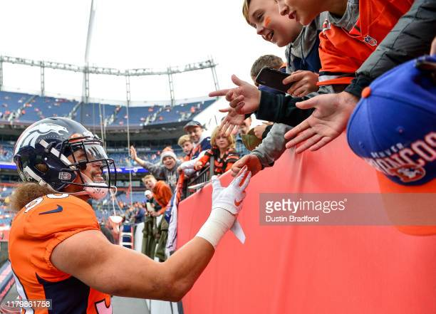 Phillip Lindsay of the Denver Broncos has a word with young fans during warm ups before a game against the Cleveland Browns at Empower Field at Mile...