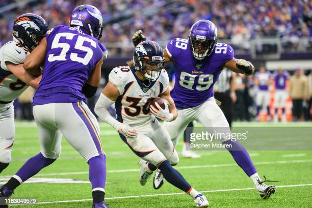 Phillip Lindsay of the Denver Broncos runs with the ball in the first quarter of the game against the Minnesota Vikings at U.S. Bank Stadium on...