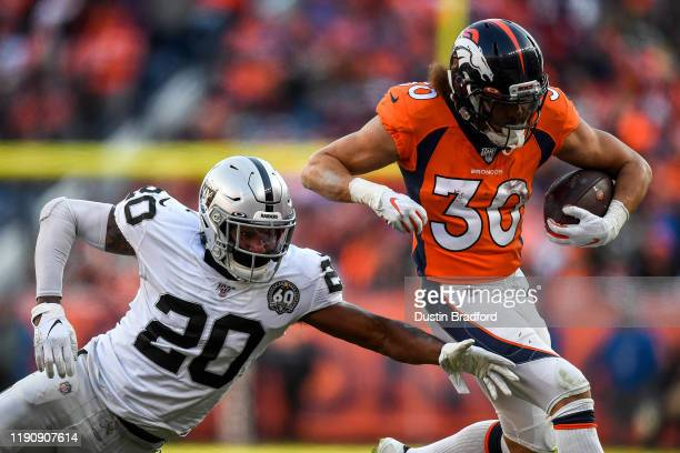 Phillip Lindsay of the Denver Broncos rushes under coverage by Daryl Worley of the Oakland Raiders at Empower Field at Mile High on December 29 2019...