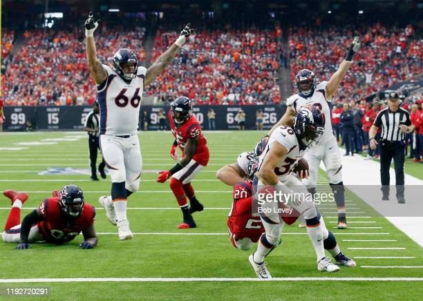 Phillip Lindsay of the Denver Broncos scores a touchdown as Justin Reid of the Houston Texans defends in the second quarter at NRG Stadium on...