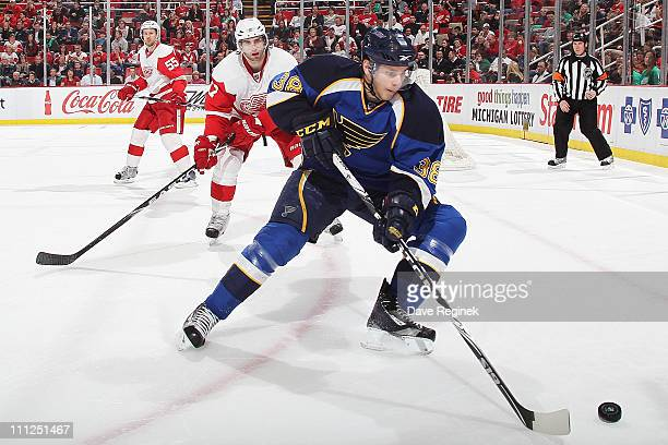 Phillip McRae of the St Louis Blues controls the puck while Patrick Eaves of the Detroit Red Wings follows after during an NHL game at Joe Louis...
