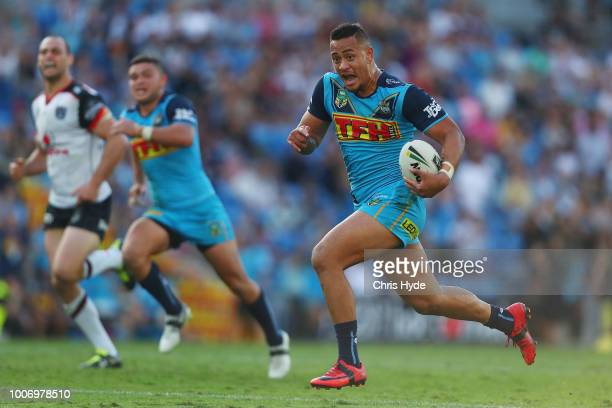 Phillip Sami of the Titans makes a break to score a try during the round 20 NRL match between the Gold Coast Titans and the New Zealand Warriors at...