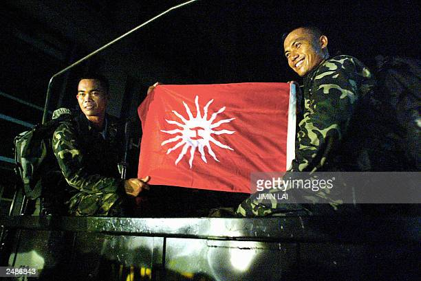 Phillipino rebel military soldiers hold their flag from the revolution against Spain called Magdalo as they sit in the rear of a truck leaving the...